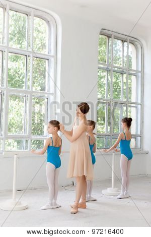 Three little ballerinas dancing with personal ballet teacher in dance studio
