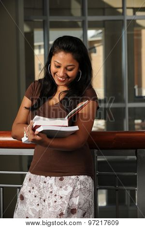 Portrait of ethnic female student reading book inside campus building