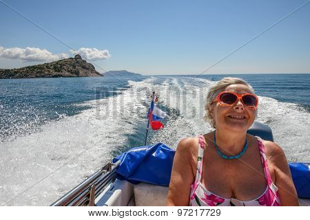 Senior Lady Is In Sea Boat On Foamy Trace Background.