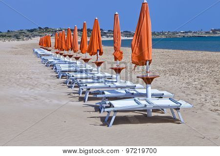 Sun orange closed umbrellas with white plastic relaxing chairs on a sandy Mediterranean beach Sicily