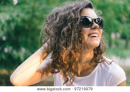 Portrait Of A Young Smiling Happy Woman In Sunglasses At The Park On A Background Of Green Trees