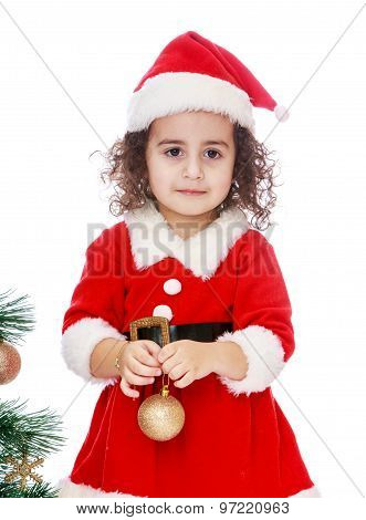Girl dressed as Santa Claus with a toy in the hands of