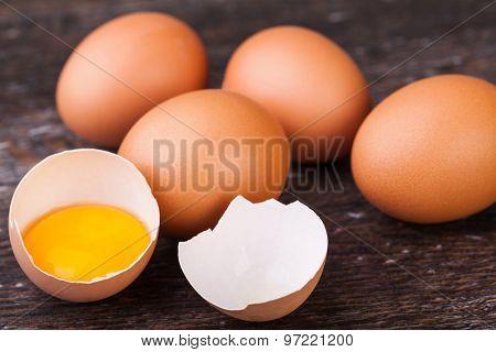 Broken eggs on a wooden background
