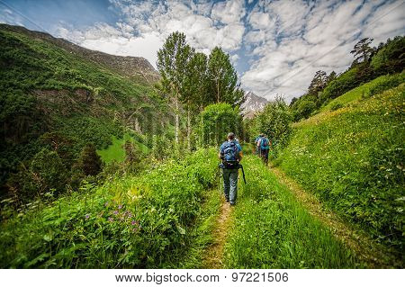 Tourists with trekking pole going on mountain Cheget