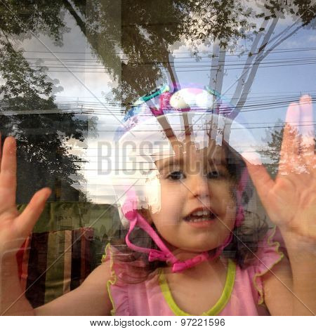 Authentic image of a toddler girl looking out a porch window with tree reflections in the Instagram filtered style
