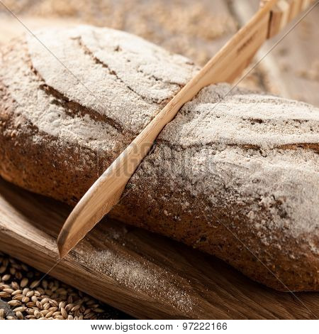 Rye Bread With Seeds On A Cutting Board, A Wooden Knife