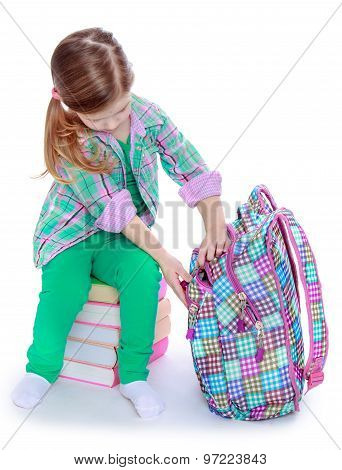 schoolgirl examines a backpack
