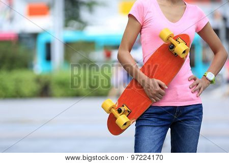young asian woman skateboarder with skateboard on city