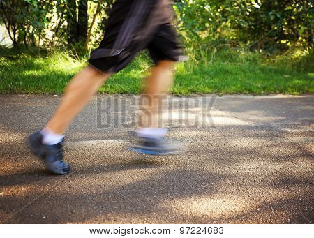 a blurred runner jogging on a bike path in nature and an urban background