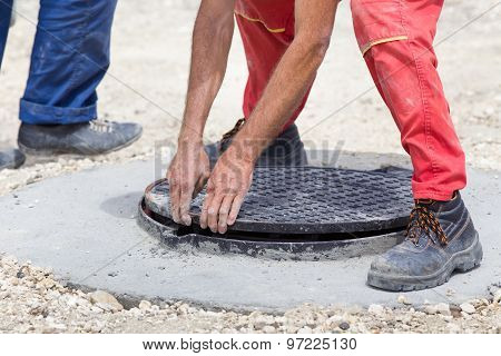 Worker Installing Cover At Manhole