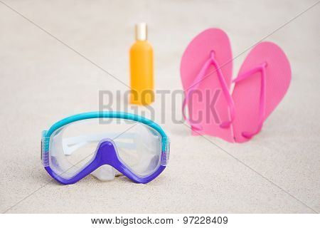 Diving Mask, Flip Flops And Suntan Lotion Bottle On Sandy Beach