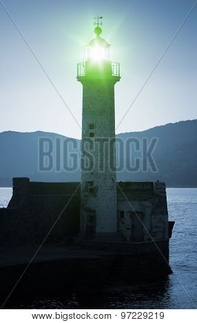 Old Lighthouse Tower Silhouette With Green Light