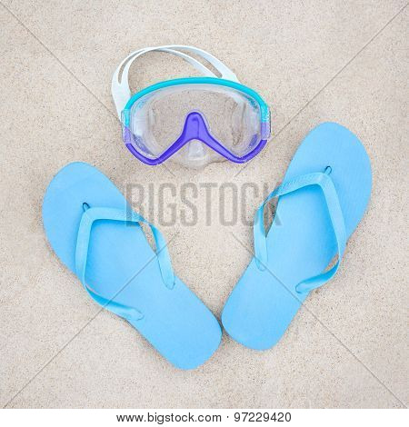 Beach Concept - Blue Flip Flops And Diving Mask On The Sand