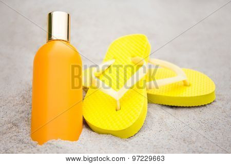 Summer And Skin Care Concept - Flip Flops And Suntan Lotion Bottle On Sandy Beach