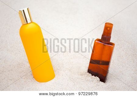 Sunbathing Concept - Suntan Lotion And Spray Bottles On Sandy Beach