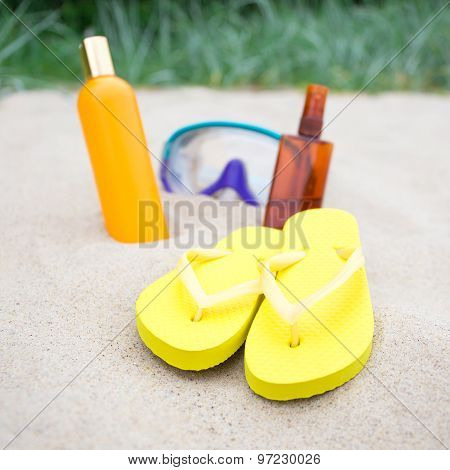 Beach Concept - Flip Flops, Suntan Lotion Bottles And Diving Mask On The Sand