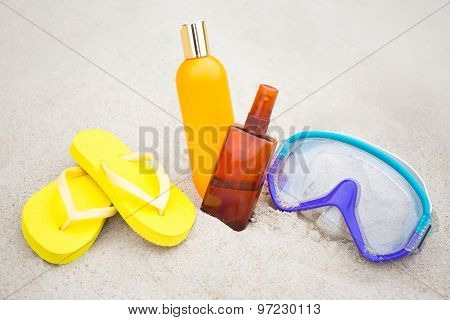 Summer Concept - Flip Flops, Suntan Lotion Bottles And Diving Mask On The Sand