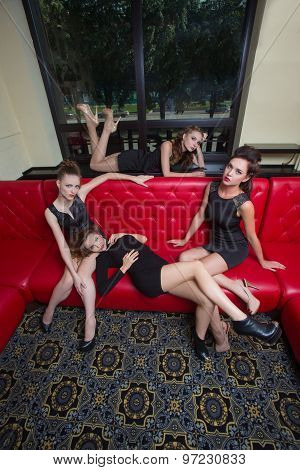 Four girl in black short dress on a red couch