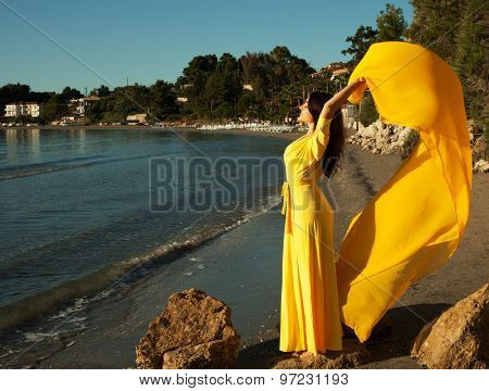 Fashion concept - Portrait of a beautiful woman with long yellow dress on a  beach.