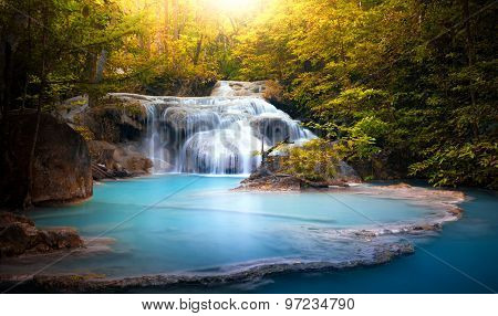 Sunlight through tree leaves lights beautiful waterfall in forest