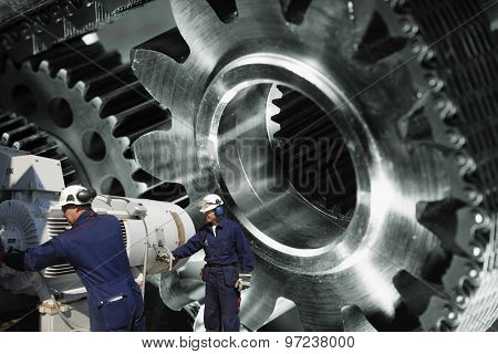 engineers, workers with machinery, large cogwheels and gears in background, focal-point on workers