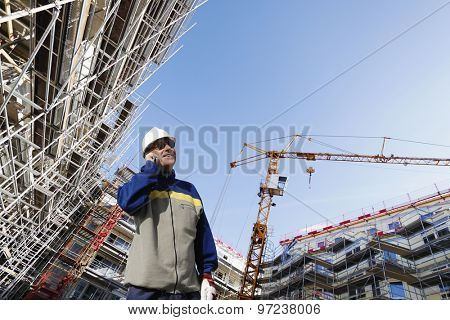 building worker talking in phone with a large construction site in background, super wide perspective