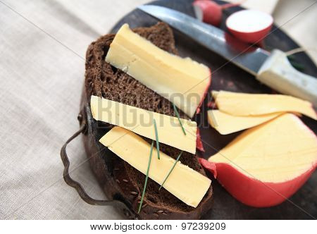 Gouda cheesee sliced from wedge on dark bread