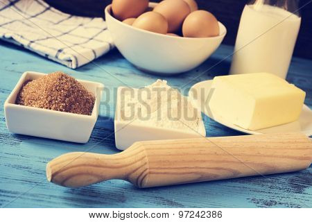 some ingredients for preparing cookies or a cake, such as milk, eggs, flour, butter and brown sugar on a blue rustic wooden surface, with a filter effect