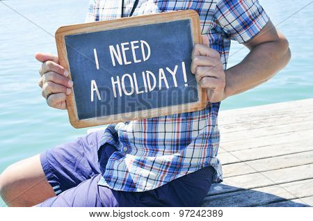 a young caucasian man sitting in a wooden pier shows a chalkboard with the text I need a holiday written in it