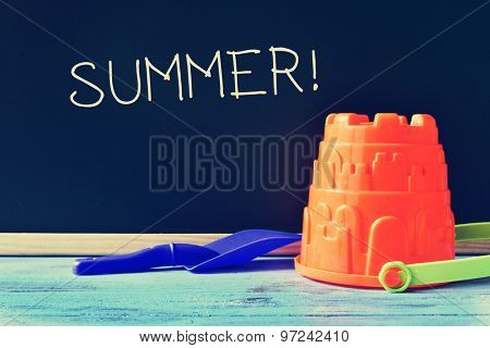 a blue toy shovel and an orange toy pail on a blue school desk, and the word summer written in a chalkboard