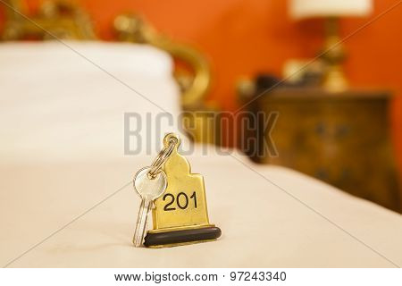Hotel Room Key Lying On Bed With Keyring