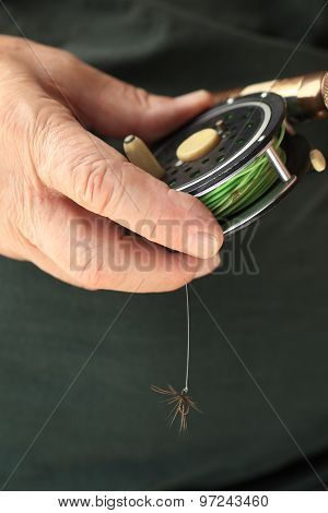 Man holds fly fishing reel and artificial fly