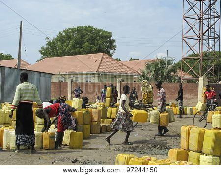 BOR, SOUTH SUDAN-JUNE 26, 2012: A crowd of unidentified people fill water jugs at a central water point in Bor, South Sudan