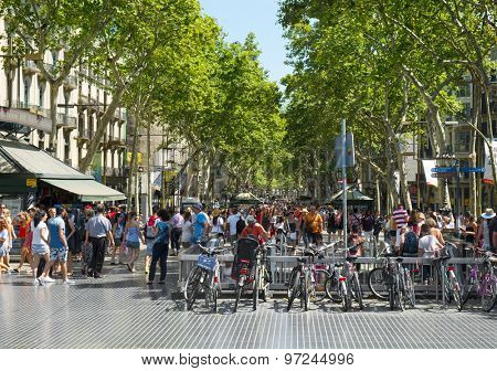 BARCELONA, SPAIN - JULY 10: A crowd in La Rambla on July 10, 2015 in Barcelona, Spain. Thousands of people walk daily by this popular pedestrian mall 1.2 kilometer-long