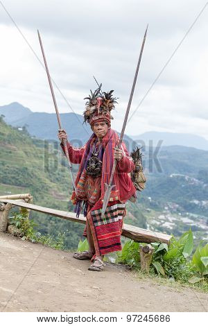 old ifugao man in national dress next to rice terraces