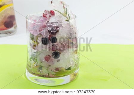 Natural Red Forest Fruit Cocktail With Ice, Lemon And Sliced Fruits In A Crooked Glass