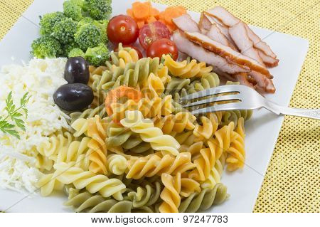 Coloured Pasta Served With Cheese,olives Broccoli, Cherry Tomatoes And Smoked Meat Slices