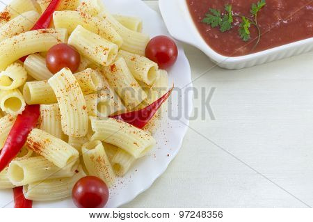 Pasta With Cherry Tomatoes And Red Pepper Served With A Tomato Sauce On A Wooden Table