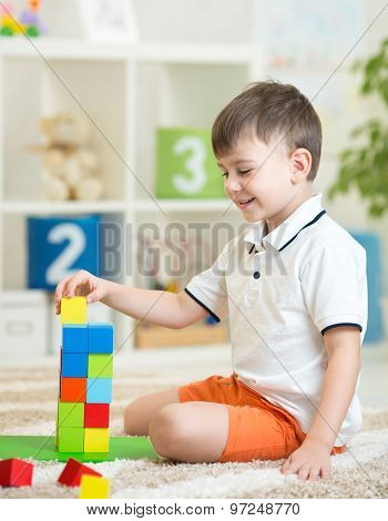 child boy playing with wooden colorful cubes