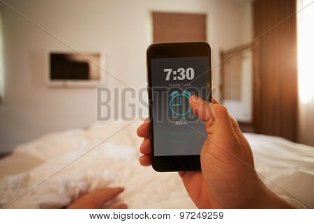 Point Of View Image Of Person In Bed Turning Off Phone Alarm