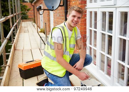 Portrait Of Decorator On Scaffolding Painting House Windows