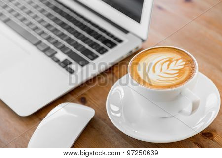 laptop with coffee cup on old wooden table