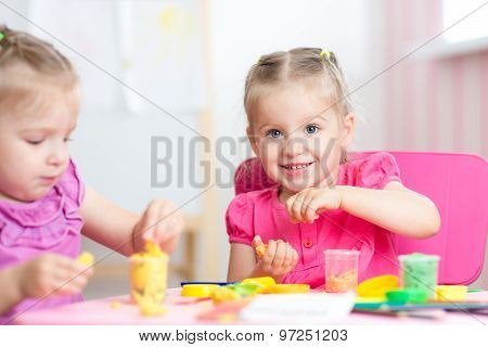 children playing with colorful clay