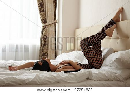 Erotic games. Catwoman posing in hotel bedroom