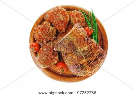 served roast meat on wooden plate with tomatoes