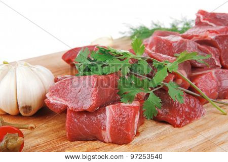 uncooked fresh beef meat chunks on wooden cutting plate with green hot and red peppers isolated over white background . shallow dof