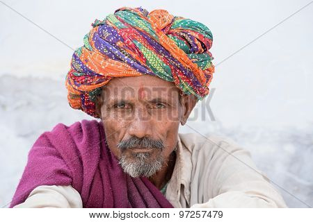 Indian Man, Sits On The Ghat Along The Sacred Sarovar Lake In Pushkar