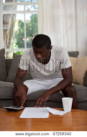 african black man sitting on sofa couch calculating home bill finances in living room