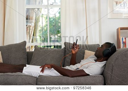 african black man listening to music relaxing on sofa couch in home living room