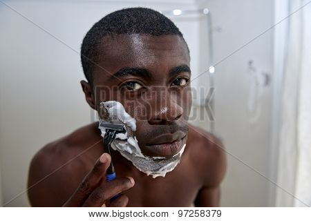 portrait of shirtless african black man shaving beard stubble face in mirror reflection for morning clean shaven look in home bathroom